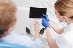 Καταλαβαίνω ικανός οδοντίατρος που χρησιμοποιεί την ταμπλέτα για την εξήγηση Στοκ φωτογραφία με δικαίωμα ελεύθερης χρήσης