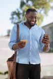 Καταλαβαίνω νεαρός άνδρας που χρησιμοποιεί το smartphone του για να καταστήσει τις αγορές σε απευθείας σύνδεση Στοκ Εικόνα