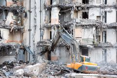 Κατεδάφιση και καταστροφή ενός χρησιμοποιώντας εκσκαφέα οικοδόμησης Εξοπλισμός καταστροφέων στοκ εικόνες