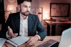 Κατειλημμένος αρμόδιος εργαζόμενος που εξετάζει το lap-top και την επικοινωνία στοκ φωτογραφία με δικαίωμα ελεύθερης χρήσης