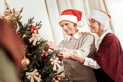 Κατειλημμένο ευχάριστο ζεύγος που στέκεται και που διακοσμεί το χριστουγεννιάτικο δέντρο στοκ εικόνα