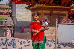 ΚΑΤΜΑΝΤΟΥ, ΝΕΠΑΛ ΣΤΙΣ 15 ΟΚΤΩΒΡΊΟΥ 2017: Μη αναγνωρισμένη νεπαλική γυναίκα που φορά τα χαρακτηριστικά ενδύματα και που φέρνει ένα Στοκ Φωτογραφίες