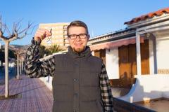 Κατοίκιση, σπίτι αγοράς, ακίνητη περιουσία και έννοια ιδιοκτησίας - όμορφο άτομο που παρουσιάζει κλειδί του στο νέο σπίτι στοκ φωτογραφία