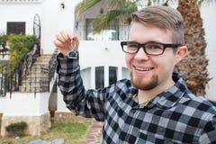 Κατοίκιση, σπίτι αγοράς, ακίνητη περιουσία και έννοια ιδιοκτησίας - όμορφο άτομο που παρουσιάζει κλειδί του στο νέο σπίτι στοκ εικόνα με δικαίωμα ελεύθερης χρήσης