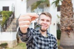 Κατοίκιση, σπίτι αγοράς, ακίνητη περιουσία και έννοια ιδιοκτησίας - όμορφο άτομο που παρουσιάζει κλειδί του στο νέο σπίτι στοκ εικόνες