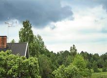 Κατοικήσιμη περιοχή κατά τη διάρκεια του καλοκαιριού Όμορφα πράσινα βλάστηση, σπίτια και σύννεφα βροχής θέμα αστικό Στοκ εικόνες με δικαίωμα ελεύθερης χρήσης