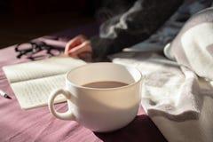 Κατοχή του καφέ και ανάγνωση στο κρεβάτι στο οκνηρό ηλιόλουστο πρωί steaming στοκ φωτογραφία με δικαίωμα ελεύθερης χρήσης