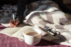 Κατοχή του καφέ και γράψιμο στο κρεβάτι στο οκνηρό ηλιόλουστο πρωί steaming στοκ εικόνες