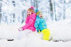 κατσίκια που παίζουν το &ch Τα παιδιά παίζουν υπαίθρια στις χειμερινές χιονοπτώσεις Στοκ Φωτογραφίες