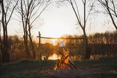Κατσαρόλα πέρα από την πυρκαγιά στη λίμνη το βράδυ στοκ εικόνες