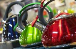 Κατσαρόλες μετάλλων με έναν συριγμό των διάφορων χρωμάτων στοκ εικόνα