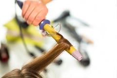 Κατσαρώνοντας τρίχα γυναικών κομμωτών με το ηλεκτρικό ρόλερ σιδήρου tong Στοκ Φωτογραφία