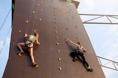 Κατώτατη άποψη δύο νέων ορειβατών που πλησιάζουν στη λήξη του σημείου στη διαδρομή ταχύτητας να αναρριχηθεί στους ανταγωνισμούς υ Στοκ Φωτογραφίες