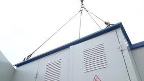 Κατώτατη άποψη ενός κιβωτίου μετασχηματιστών που περιστρέφεται στον αέρα που αναστέλλεται σε έναν γερανό κατασκευής φιλμ μικρού μήκους