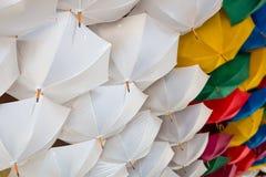 Κατώτατη άποψη σχετικά με το μεγάλο αριθμό άσπρων και χρωματισμένων ομπρελών Στοκ εικόνα με δικαίωμα ελεύθερης χρήσης