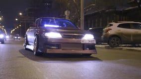 Κατώτατη άποψη της δροσερής οδήγησης αυτοκινήτων στην πόλη νύχτας r Ο λαμπρός σκοτεινός χρυσός τελειώνει με ακτινοβολεί στην οδήγ απόθεμα βίντεο