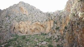 Κατώτατη άποψη του απότομου βράχου στο υπόβαθρο του ουρανού Τέχνη Από το δύσκολο βουνό με την πρασινάδα στο πόδι και τους αραιούς φιλμ μικρού μήκους