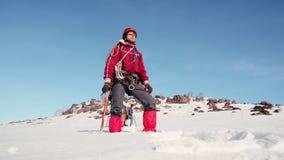 Κατώτατη άποψη του γενειοφόρου ορειβάτη, ο οποίος εξετάζει την απόσταση και τις στροφές στην πλευρά είναι ντυμένος στα θερμά ενδύ απόθεμα βίντεο