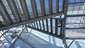 Κατώτατη κάμερα άποψη 360 βαθμού σχετικά με το άτομο στο κοστούμι που χρησιμοποιεί αναρριμένος στα σύγχρονα σκαλοπάτια αρχιτεκτον απόθεμα βίντεο