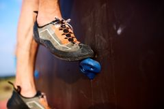 Κατώτατη στενή επάνω άποψη του ποδιού ορειβατών βράχου τοίχο αναρρίχησης κατάρτισης στον τεχνητό υπαίθρια Αρσενικά πόδια να αναρρ Στοκ Φωτογραφία