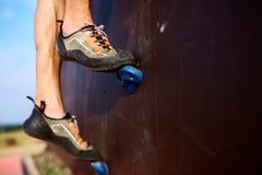 Κατώτατη στενή επάνω άποψη του ποδιού ορειβατών βράχου τοίχο αναρρίχησης κατάρτισης στον τεχνητό υπαίθρια Αρσενικά πόδια να αναρρ Στοκ εικόνα με δικαίωμα ελεύθερης χρήσης