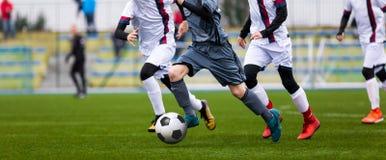 Κατώτερος αγώνας ποδοσφαίρου Παιχνίδι ποδοσφαίρου για τους παίκτες νεολαίας Αγόρια που παίζουν τον αγώνα ποδοσφαίρου στην πίσσα π Στοκ Εικόνες
