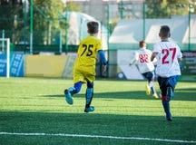 Κατώτερος αγώνας ποδοσφαίρου Παιχνίδι ποδοσφαίρου για τους παίκτες νεολαίας Αγόρια στον κίτρινο και άσπρο ομοιόμορφο παίζοντας αγ στοκ εικόνες