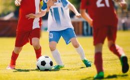 Κατώτερος ανταγωνισμός αγώνων ποδοσφαίρου Δύο νέοι ποδοσφαιριστές που τρέχουν και που ανταγωνίζονται για τη σφαίρα Στοκ εικόνα με δικαίωμα ελεύθερης χρήσης
