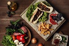Κατ' οίκον γίνοντα χάμπουργκερ με τις τηγανιτές πατάτες, ντομάτες κερασιών Στοκ Εικόνα