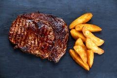 Κατ' οίκον μαγειρευμένη μέση σπάνια ψημένη στη σχάρα μπριζόλα Ribeye βόειου κρέατος με την ψημένη πατάτα στο υπόβαθρο μπλε πετρών Στοκ Φωτογραφίες