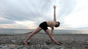 Καυκάσια αθλητική γιόγκα άσκησης γυναικών στην ακτή του τροπικού ωκεανού r E απόθεμα βίντεο