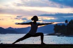 Καυκάσια γιόγκα άσκησης γυναικών στην ακτή στοκ φωτογραφία