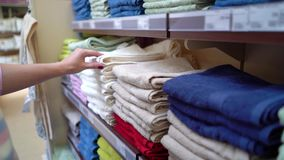 Καυκάσια γυναίκα κοντά στα ράφια καταστημάτων που επιλέγει την πετσέτα στην κινηματογράφηση σε πρώτο πλάνο καταστημάτων φιλμ μικρού μήκους