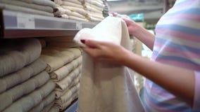 Καυκάσια γυναίκα κοντά στα ράφια καταστημάτων που επιλέγει την πετσέτα στην κινηματογράφηση σε πρώτο πλάνο καταστημάτων απόθεμα βίντεο