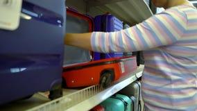 Καυκάσια γυναίκα κοντά στα ράφια καταστημάτων που επιλέγει τη βαλίτσα στην αγορά ψιλικών απόθεμα βίντεο