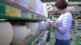 Καυκάσια γυναίκα κοντά στα ράφια καταστημάτων που επιλέγει το κεραμικό δοχείο για την οικογένεια στο κατάστημα απόθεμα βίντεο