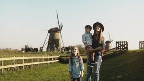 Καυκάσια γυναίκα με δύο παιδιά κοντά σε ένα αγρόκτημα ανεμόμυλων Η μητέρα, το μικρό παιδί και το χαριτωμένο κορίτσι εξερευνούν τα απόθεμα βίντεο