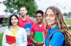 Καυκάσια γυναίκα σπουδαστής με την ομάδα multiethnic σπουδαστών στοκ φωτογραφία με δικαίωμα ελεύθερης χρήσης