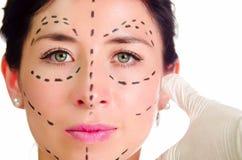 Καυκάσια γυναίκα Headshot με τις διαστιγμένες γραμμές που σύρονται γύρω από το πρόσωπο που εξετάζει τη κάμερα, χέρια γιατρών που  Στοκ Φωτογραφίες