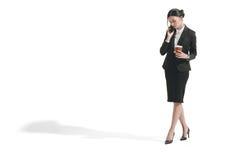 Καυκάσια επιχειρηματίας που μιλά στο smartphone κρατώντας το φλυτζάνι καφέ εγγράφου Στοκ φωτογραφία με δικαίωμα ελεύθερης χρήσης