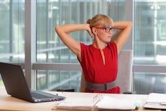 Καυκάσια επιχειρησιακή γυναίκα eyeglasses που χαλαρώνει το λαιμό, τεντώνοντας τα όπλα Στοκ Εικόνες