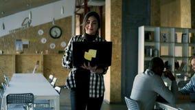 Καυκάσια θετική γυναίκα που απασχολείται δημόσια στον εργασιακό χώρο με το εσωτερικό τουβλότοιχος Όμορφο νέο brunette στο πουκάμι απόθεμα βίντεο