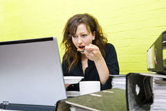 Καυκάσια νέα γυναίκα που τρώει και που εργάζεται στο φορητό προσωπικό υπολογιστή της στο γραφείο της Στοκ φωτογραφία με δικαίωμα ελεύθερης χρήσης