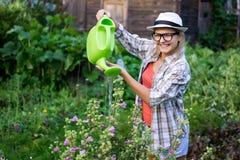 Καυκάσια νέα κυρία με τα γυαλιά και τα λουλούδια ποτίσματος καπέλων στοκ φωτογραφίες με δικαίωμα ελεύθερης χρήσης