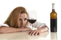 Καυκάσια ξανθή σπαταλημένη καταθλιπτική οινοπνευματώδης γυναίκα που πίνει τον εθισμό οινοπνεύματος γυαλιού κόκκινου κρασιού Στοκ Φωτογραφία