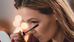 Καυκάσια πρότυπα ξανθά χρώματα eyelashes με mascara Επιχειρησιακή γυναίκα Makeup Σε αργή κίνηση στο υπόβαθρο των Χριστουγέννων φιλμ μικρού μήκους
