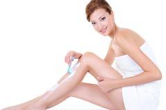 Καυκάσια πόδια ξυρίσματος γυναικών με το ξυράφι Στοκ φωτογραφία με δικαίωμα ελεύθερης χρήσης