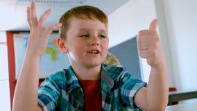 Καυκάσια συνεδρίαση μαθητών στο γραφείο και υπολογισμός με το δάχτυλό του σε μια τάξη απόθεμα βίντεο