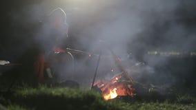 Καυκάσια συνεδρίαση ατόμων δίπλα στη φωτιά και ομιλία στο έξυπνο τηλέφωνο τη νύχτα απόθεμα βίντεο