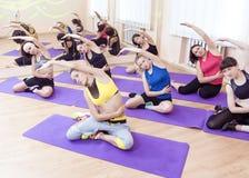 Καυκάσιες αθλητικές γυναίκες Ομάδων των Επτά που τεντώνουν στο εσωτερικό Στοκ Εικόνες